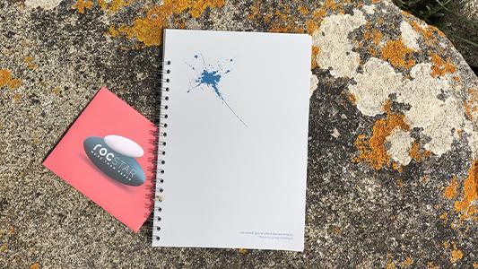 Un cahier rocStar en papier minéral, posé sur un rocher